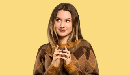 Teenager girl with brown sweater scheming something over isolated yellow background