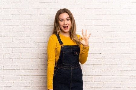 Teenager girl over white brick wall showing ok sign with fingers Imagens
