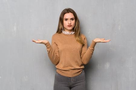 Adolescente sur un mur texturé mécontente parce qu'elle ne comprend pas quelque chose
