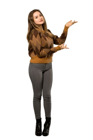 A full-length shot of a Teenager girl with brown sweater extending hands to the side for inviting to come over isolated white background