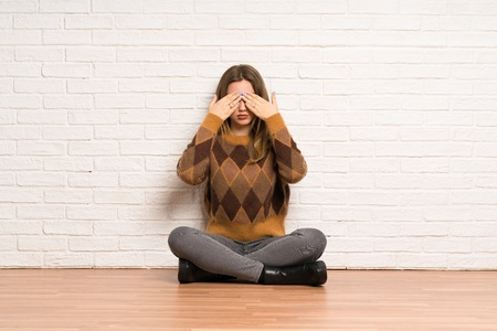 Teenager girl sitting on the floor covering eyes by hands. Do not want to see something