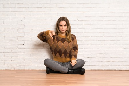 Teenager girl sitting on the floor showing thumb down