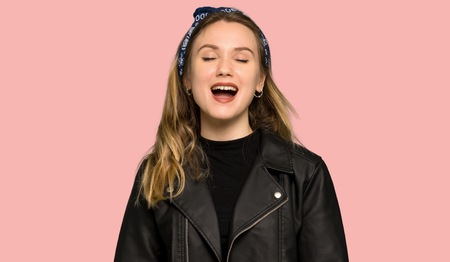 Teenager girl with leather jacket shouting to the front with mouth wide open on isolated pink background