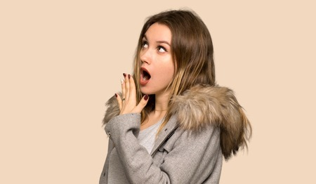 Teenager girl with coat yawning and covering wide open mouth with hand on isolated yellow background