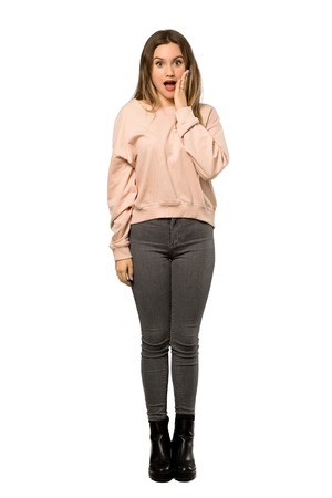 A full-length shot of a Teenager girl with pink sweater with surprise and shocked facial expression over isolated white background