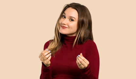 Teenager girl with turtleneck making money gesture over isolated ocher background Stock Photo