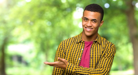 Young afro american man presenting an idea while looking smiling towards in a park