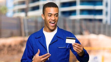 Młody afro amerykański pracownik mężczyzna trzyma kartę kredytową i zaskoczony na placu budowy