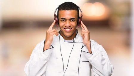Young afro american chef man listening to music with headphones on unfocused background