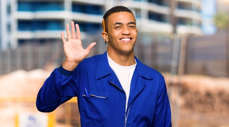 Young afro american worker man saluting with hand with happy expression in a construction site