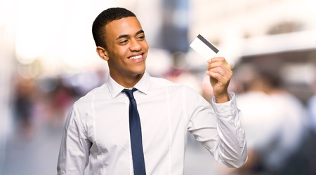 Young afro american businessman holding a credit card and thinking in the city
