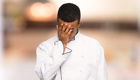 Young afro american chef man with tired and sick expression on unfocused background Banque d'images