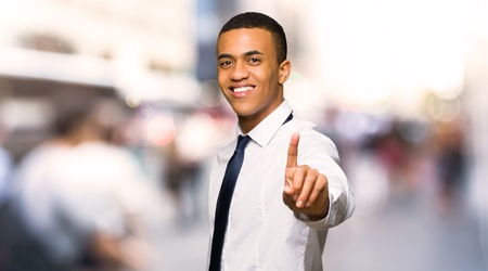 Young afro american businessman showing and lifting a finger in the city