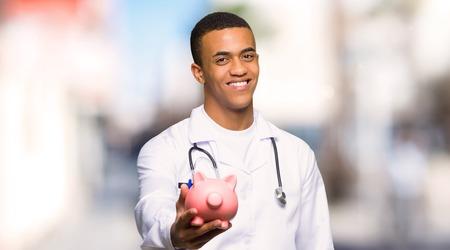 야외에서 돼지 저금통을 들고 젊은 아프리카계 미국인 의사