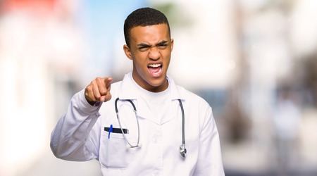 Young afro american man doctor frustrated by a bad situation and pointing to the front at outdoors 写真素材
