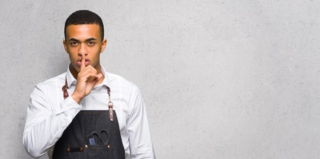 Young afro american barber man showing a sign of silence gesture putting finger in mouth on textured wall Stock Photo