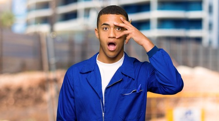 Young afro american worker man with surprise and shocked facial expression in a construction site