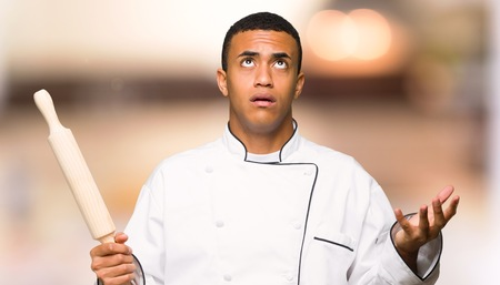 Young afro american chef man frustrated by a bad situation on unfocused background