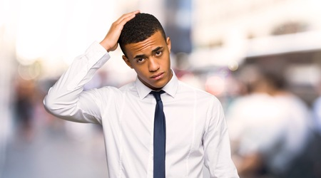 Young afro american businessman with an expression of frustration and not understanding in the city Stock Photo
