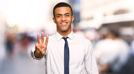 Young afro american businessman happy and counting three with fingers in the city