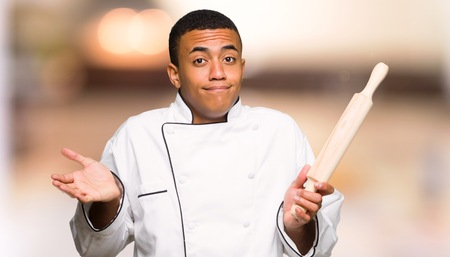 Young afro american chef man making unimportant gesture while lifting the shoulders on unfocused background