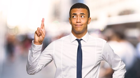 Young afro american businessman with fingers crossing and wishing the best in the city