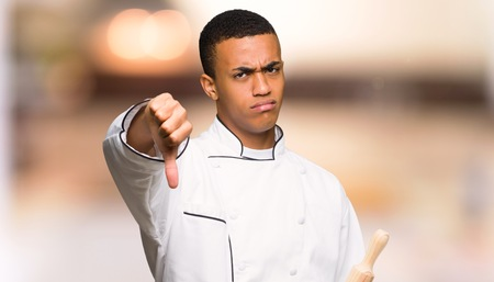 Young afro american chef man showing thumb down sign with negative expression on unfocused background