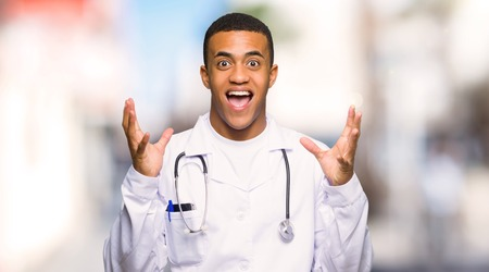 Young afro american man doctor with surprise and shocked facial expression at outdoors Фото со стока