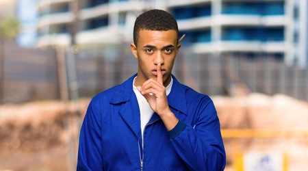 Young afro american worker man showing a sign of silence gesture putting finger in mouth in a construction site