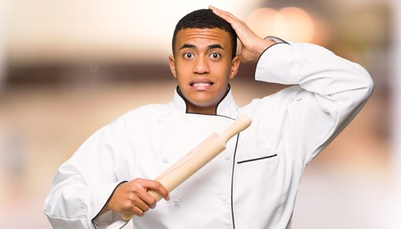 Young afro american chef man takes hands on head because has migraine on unfocused background