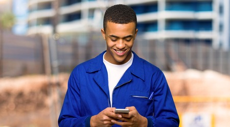 Young afro american worker man sending a message with the mobile in a construction site Archivio Fotografico