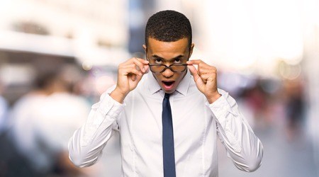Young afro american businessman with glasses and surprised in the city