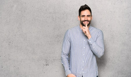 Elegant man with shirt showing a sign of silence gesture over textured wall
