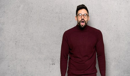 Handsome man with glasses with surprise and shocked facial expression over textured wall Stok Fotoğraf