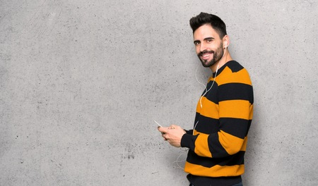 Handsome man with striped sweater sending a message with the mobile over textured wall Standard-Bild