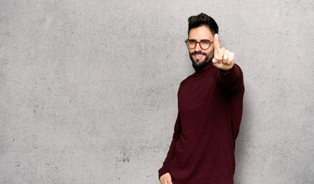 Handsome man with glasses showing and lifting a finger over textured wall Banco de Imagens
