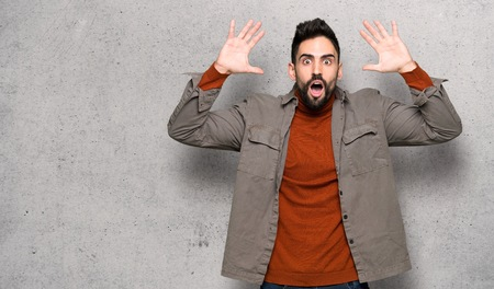 Handsome man with beard with surprise and shocked facial expression over textured wall Stok Fotoğraf