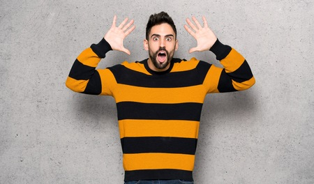 Handsome man with striped sweater with surprise and shocked facial expression over textured wall