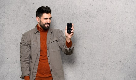 Handsome man with beard with troubled holding broken smartphone over textured wall Imagens