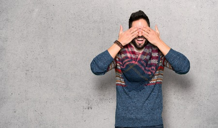 Hippie man covering eyes by hands. Surprised to see what is ahead over textured wall