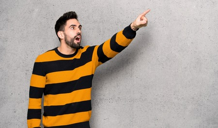 Handsome man with striped sweater pointing away over textured wall