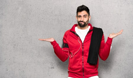 Handsome sportman having doubts while raising hands and shoulders over textured wall