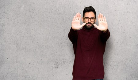 Handsome man with glasses making stop gesture for disappointed with an opinion over textured wall