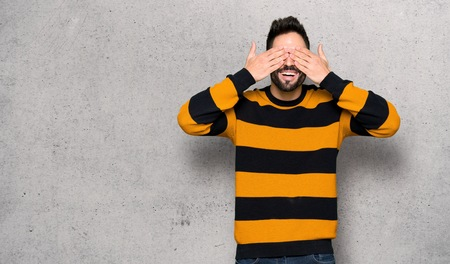 Handsome man with striped sweater covering eyes by hands. Surprised to see what is ahead over textured wall