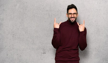 Handsome man with glasses making rock gesture over textured wall