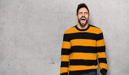 Handsome man with striped sweater shouting to the front with mouth wide open over textured wall