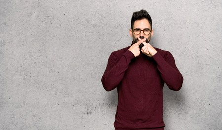 Handsome man with glasses showing a sign of silence gesture over textured wall