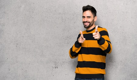Handsome man with striped sweater pointing to the front and smiling over textured wall