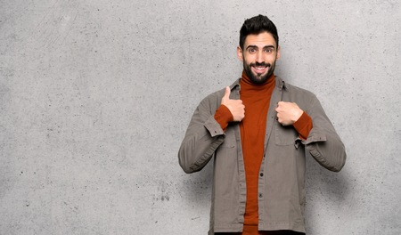 Handsome man with beard with surprise facial expression over textured wall