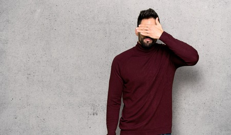 Handsome man with glasses covering eyes by hands. Do not want to see something over textured wall